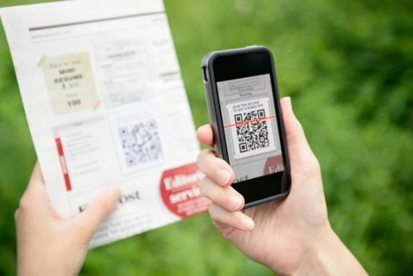Person scanning QR code with a scanning mobile app